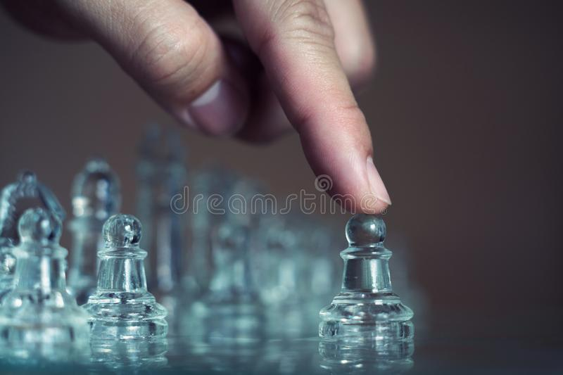 Chess board game made of glass, business competitive concept. Copy space white transparent transparency pieces king queen knight pawn rook hand finance stock photography
