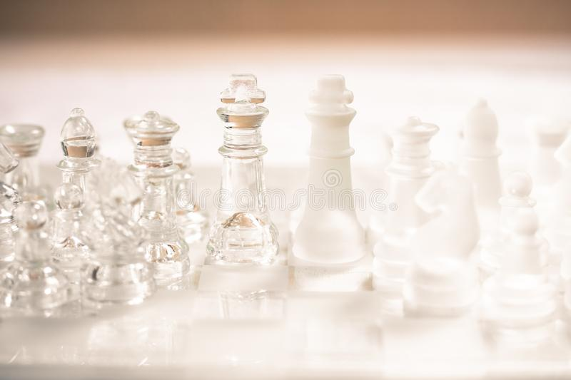 Chess board game made of glass, business competitive concept. Copy space white transparent transparency pieces king queen knight pawn rook hand finance royalty free stock image