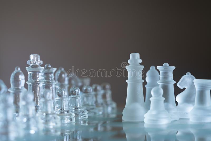 Chess board game made of glass, business competitive concept. Copy space, white, transparent, transparency, pieces, king, queen, knight, pawn, rook, hand royalty free stock photos