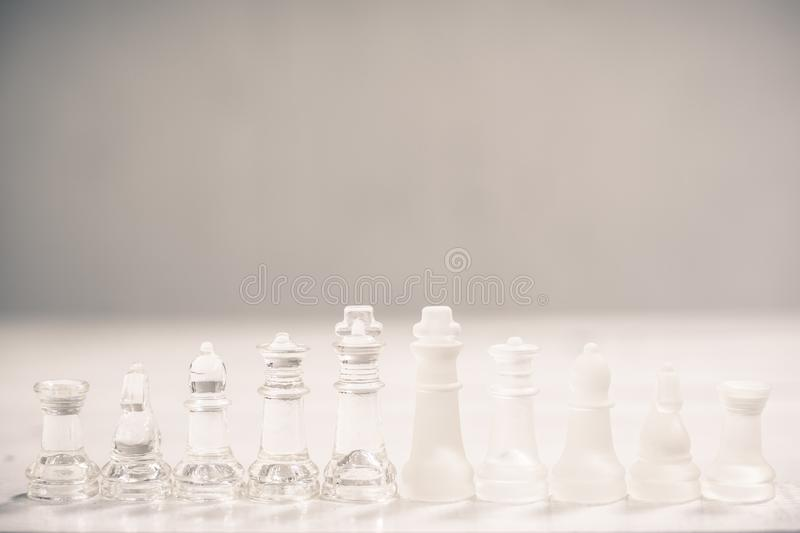 Chess board game made of glass, business competitive concept. Copy space, white, transparent, transparency, pieces, king, queen, knight, pawn, rook, hand royalty free stock image