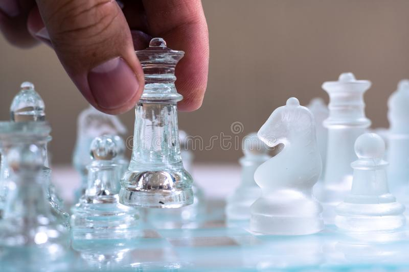 Chess board game made of glass, business competitive concept. Copy space, white, transparent, transparency, pieces, king, queen, knight, pawn, rook, hand stock image