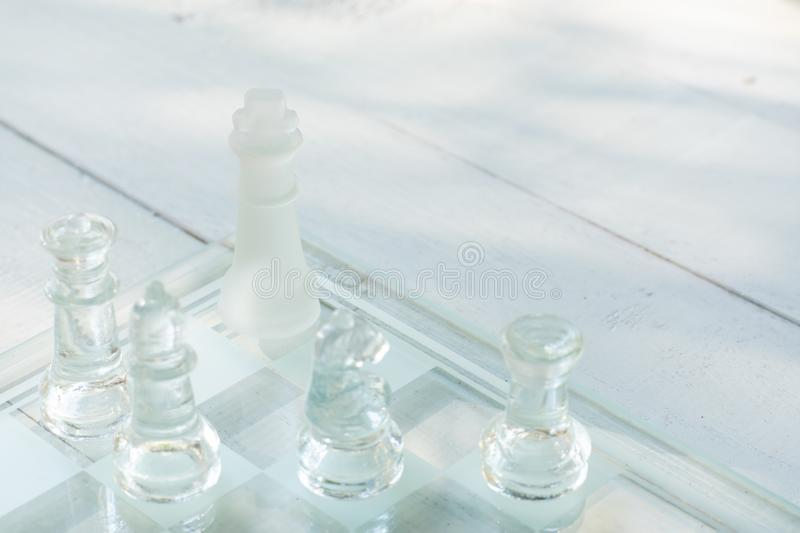 Chess board game made of glass, business competitive concept. Copy space, white, transparent, transparency, pieces, king, queen, knight, pawn, rook, hand stock photos