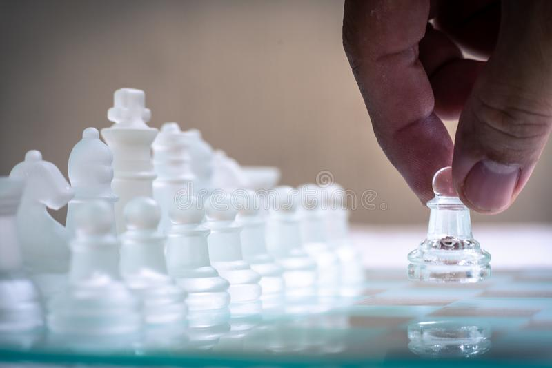 Chess board game made of glass, business competitive concept. Copy space, white, transparent, transparency, pieces, king, queen, knight, pawn, rook, hand stock photo