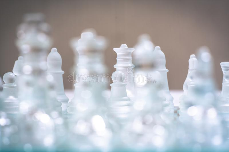 Chess board game made of glass, business competitive concept. Copy space, white, transparent, transparency, pieces, king, queen, knight, pawn, rook, hand stock photography