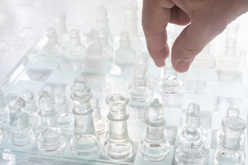 Chess board game made of glass, business competitive concept. Copy space white transparent transparency pieces king queen knight pawn rook hand finance royalty free stock images