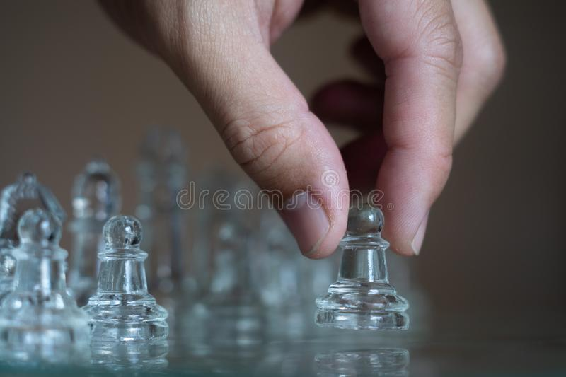 Chess board game made of glass, business competitive concept. Copy space, white, transparent, transparency, pieces, king, queen, knight, pawn, rook, hand royalty free stock images