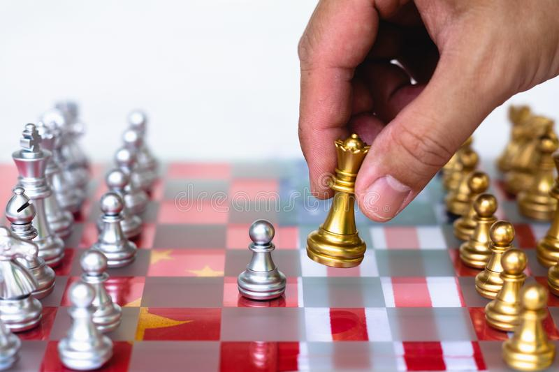 Chess board game pieces on USA and China flag background, trade war tension situation concept stock image