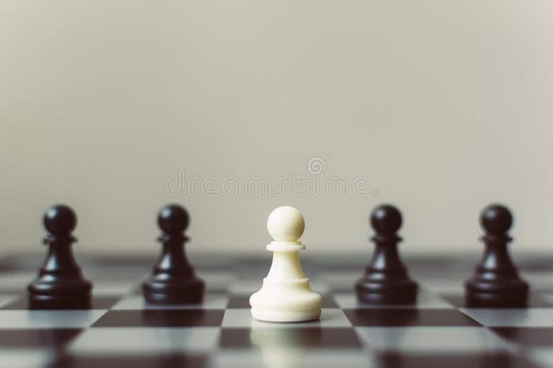 Chess board game white pawn different black pawn, Unique, think. Different, individual and standing out from the crowd concept stock photos