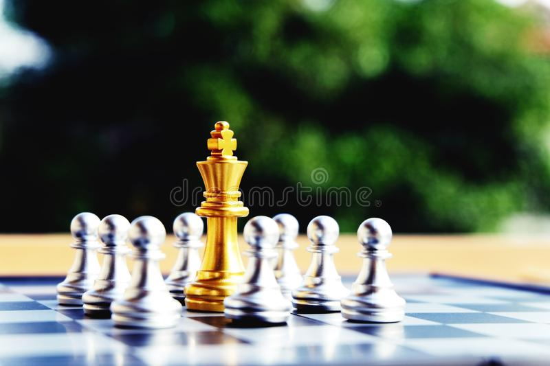 Chess board, golden king is in big troubles. Top view. Chess board, golden king is in troubles. Been surrounded by silver pawns. Referring to business's stock images