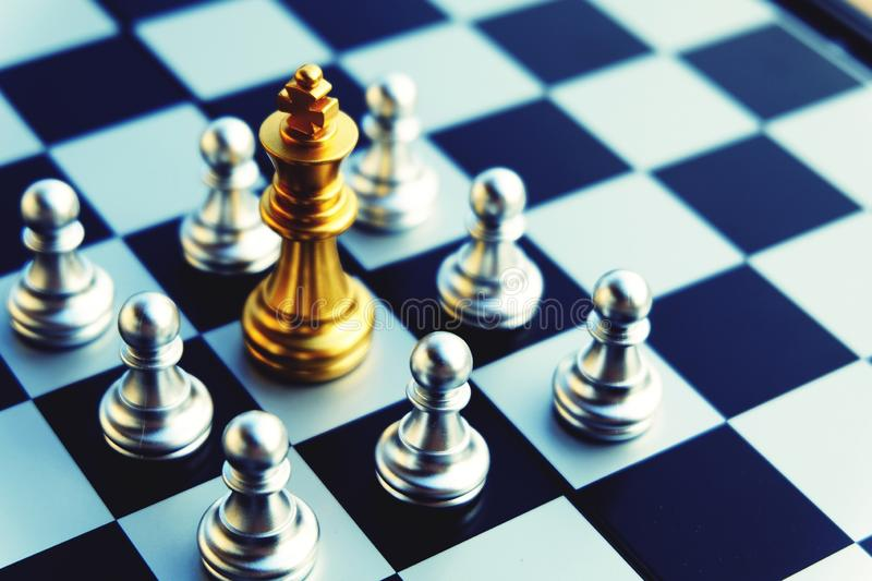 Chess board, golden king is in big troubles. Top view. Chess board, golden king is in troubles. Been surrounded by silver pawns. Referring to business's stock photography