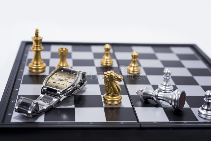 Chess Board isolated on white background. Golden and silver figures with hand watch royalty free stock photography