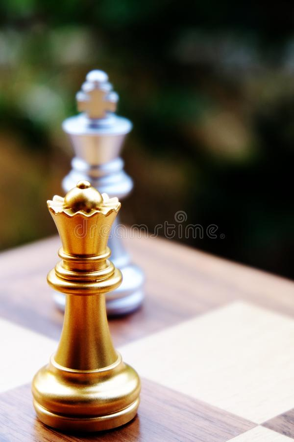Chess board king. Queen stand against the king. Focus on Queen. Business planning and strategic concept royalty free stock images