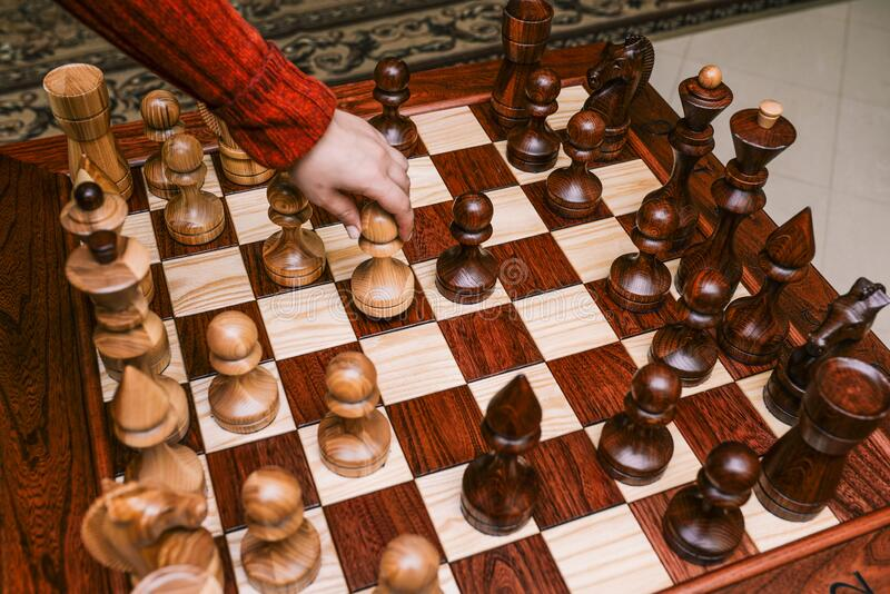 Chess board with large pieces. Game of chess. Man`s hand takes a step by pawn. Set of chess pieces.  stock photo