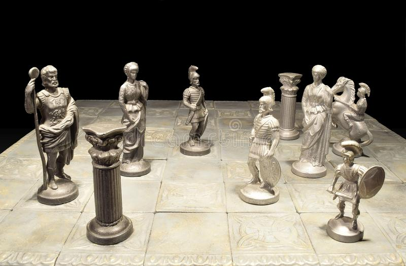 Chess board. Old Roman handmade pewter chess set royalty free stock photos