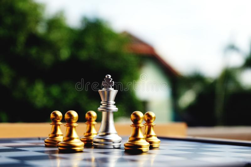 Chess board, silver king is in big troubles. Chess board, Silver king is in troubles. Been surrounded by golden pawns. Referring to business's obstacle or stock image
