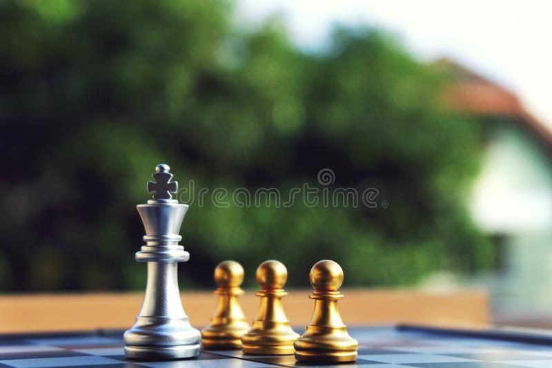 Chess board, silver king stand at front of three pawn royalty free stock image