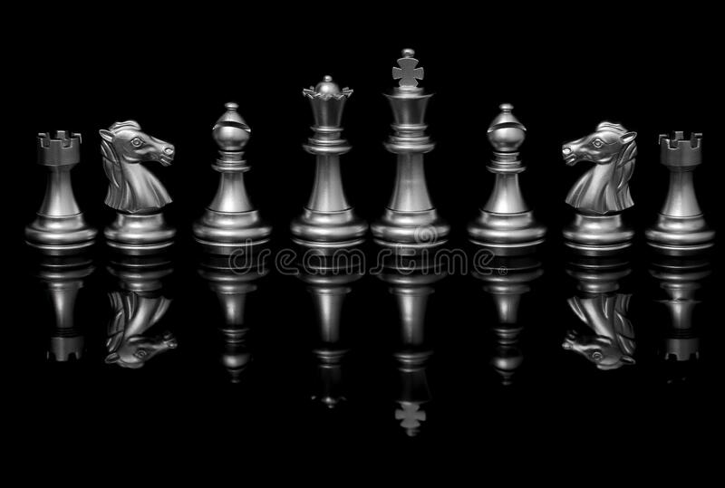 Chess board and silver pieces on black background. Chess board with beautiful chrome of silver color pieces presented on black backdrop royalty free stock photos