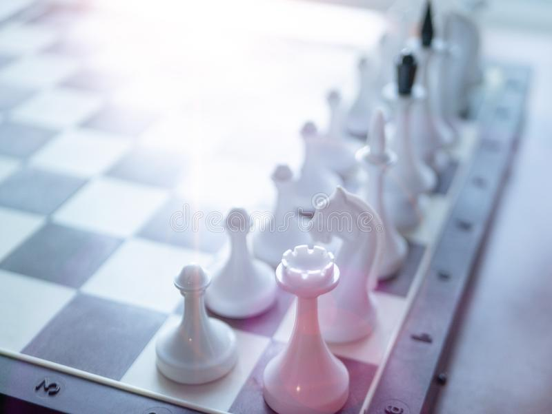 Chess board with only white figures. selective focus on nearest figure and light leak coming from top stock photos