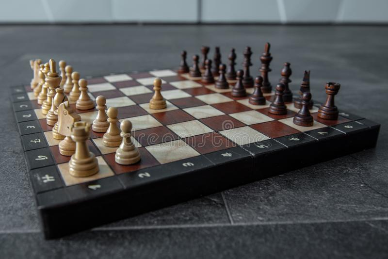 Chess board with wooden pieces. Chess board with all wooden pieces on the floor stock image