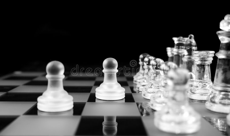 Chess - The Brave two. Glass Chess Pieces on a Frosted Glass Chess Board stock photo