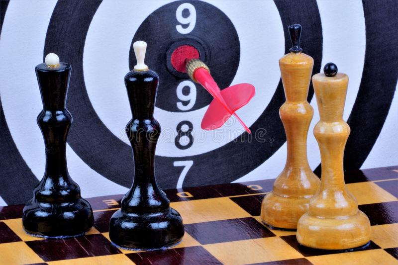 Chess, on a checkered Board king and Queen, on the background of the game of Darts.  Chess is a popular ancient Board logic stock photography