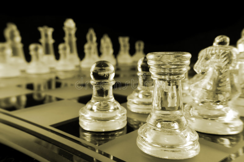 Chess - Cornered. Glass Chess Pieces on a Frosted Glass Chess Board royalty free stock photography