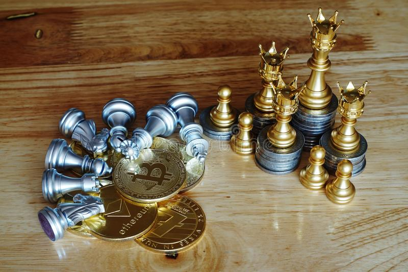 Chess with crown stand over the pile of coins, whilst opposite team fall down over bitcoin. Cash is king concept stock image