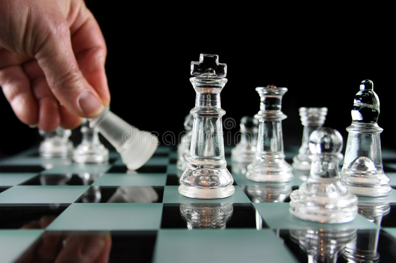 Chess - Defeated. Glass Chess Pieces on a Frosted Glass Chess Board royalty free stock image