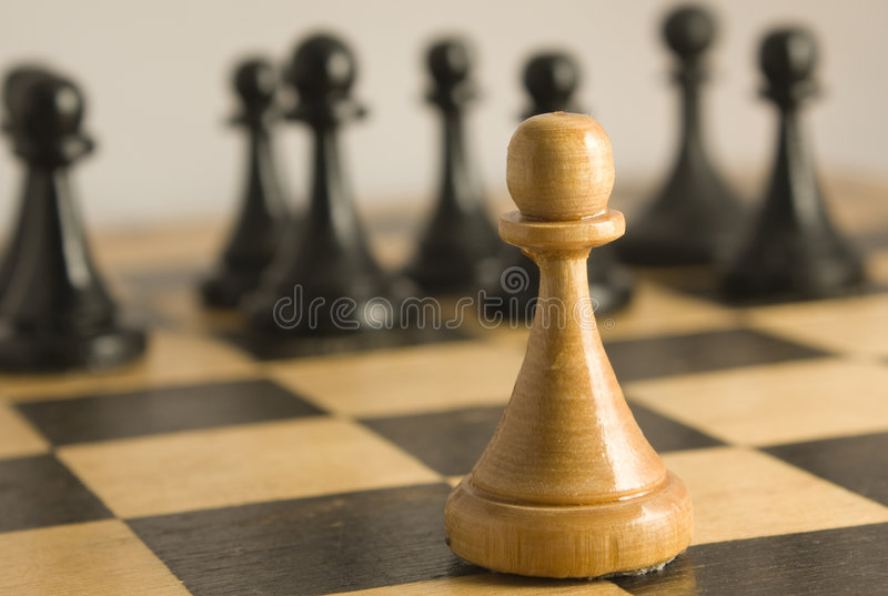 Chess exception to the rules. The white pawn resists to black pawns and is on crossing of squares. Against rules royalty free stock photography