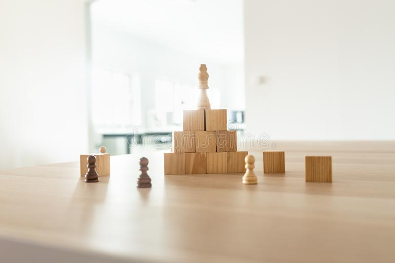 Chess figure of king placed on top of pyramid made of wooden blocks. In a conceptual image of business power and leadership stock photography