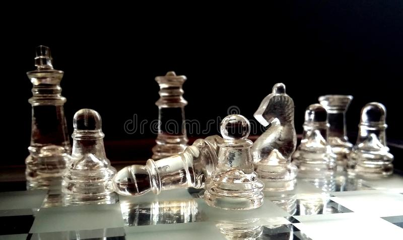 Chess figures. On a glass table royalty free stock photo