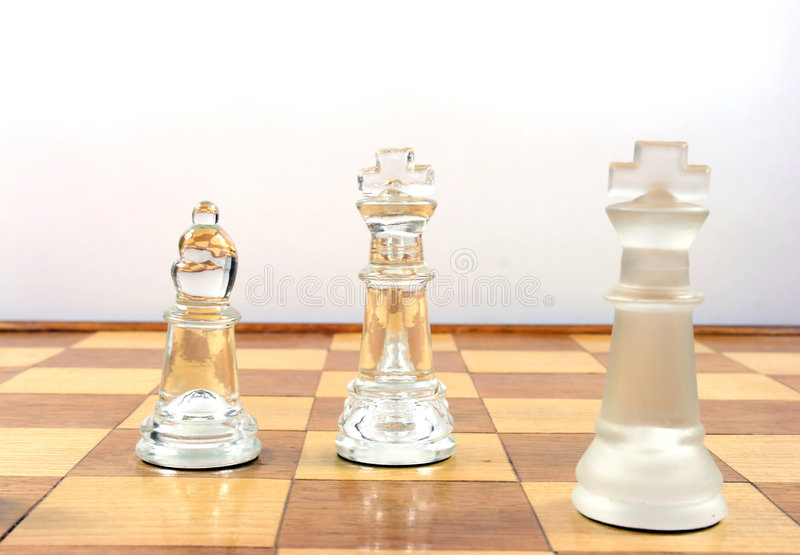 Chess Game -. Glass Chess Pieces on a wooden chessboard stock photos