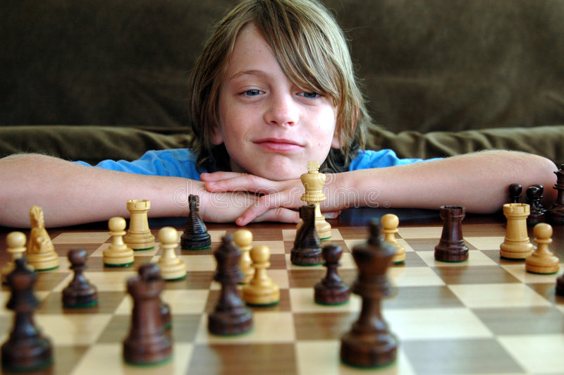 Chess game. A happy boy thinking about his next chess move stock images