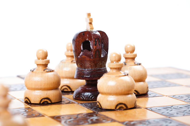 Chess game with black king surrounded by opposing pawn. Chess Game with lonely black King surrounded by opposing pawns, white background, isolated, space for stock photo