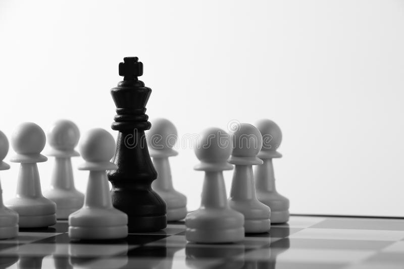 Chess game. Black king is surrounded by white pawn chess pieces on a chess board stock photo