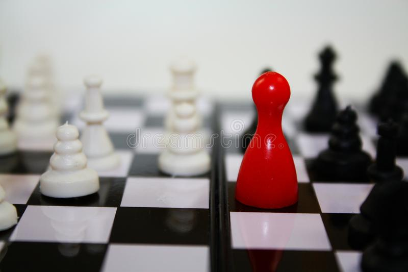 Chess game with bright red figurine for ludo on chessboard with other chess pieces. royalty free stock images
