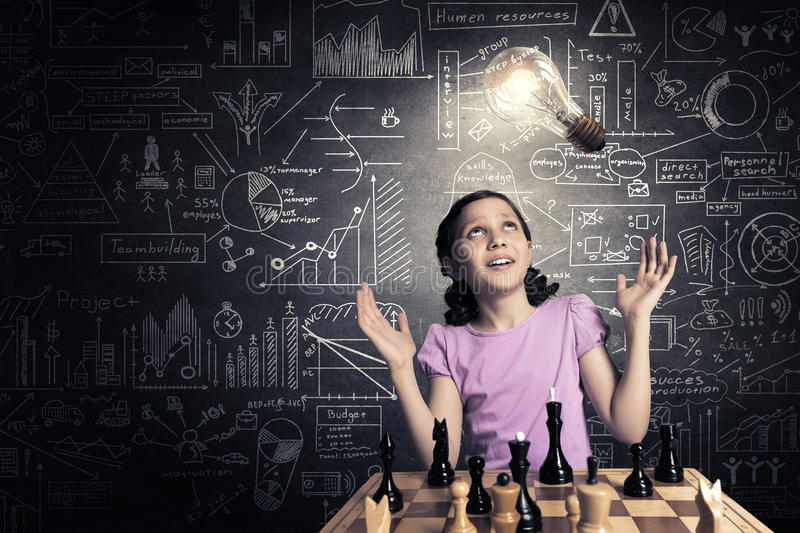 Chess game for clever mind. Young caucasian kid girl playing game of chess stock photo