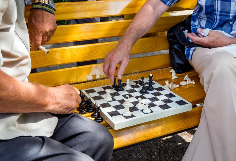 Chess game closeup on a city park bench royalty free stock image