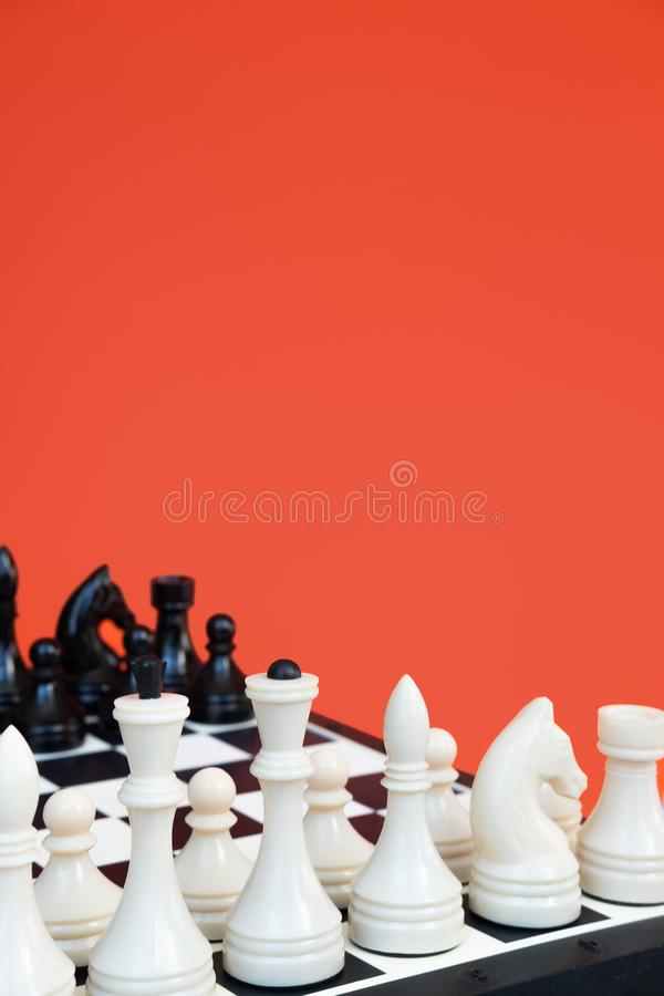 Chess game concept. Chess board with figures on orange background top view copy space. Chess game concept. Chess board with figures on orange background top stock photography
