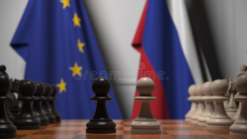 Flags of the EU and Russia behind chess board. The first pawn moves in the beginning of the game. Political rivalry. Chess game. The first pawn moves. Board stock photo