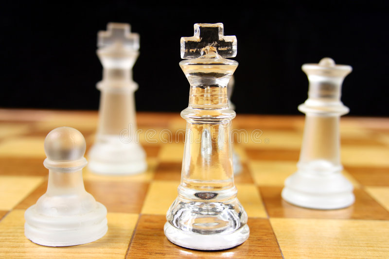 Chess Game - Focus on the King 2. Chess Game - Glass Chess Pieces on a wooden chessboard royalty free stock photos