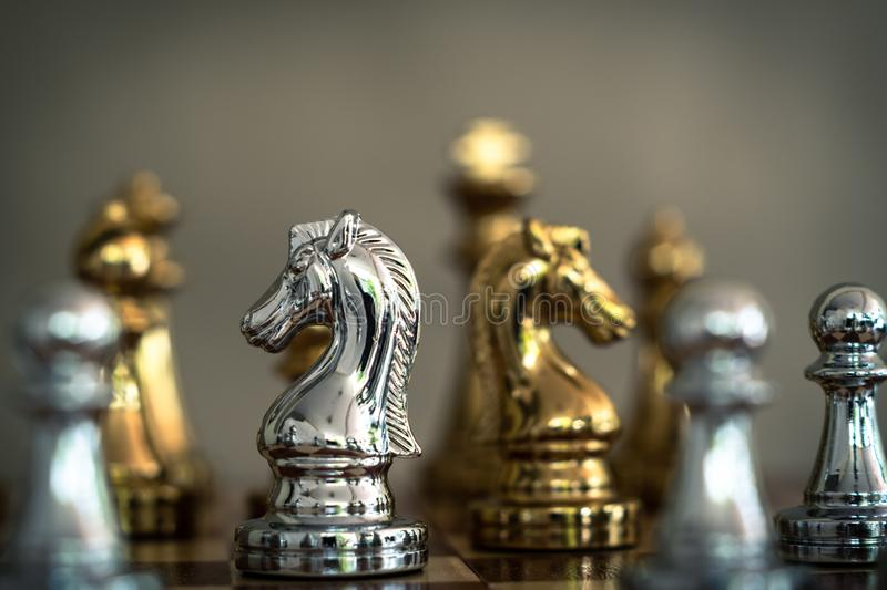 Chess game. A knight stand determinedly among the enemies. Business competitive concept. Achievement adrenaline ahead ambition brave challenge champion chance stock images