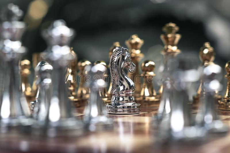 Chess game. A knight stand determinedly among the enemies. Business competitive concept. Achievement adrenaline ahead ambition brave challenge champion chance royalty free stock images