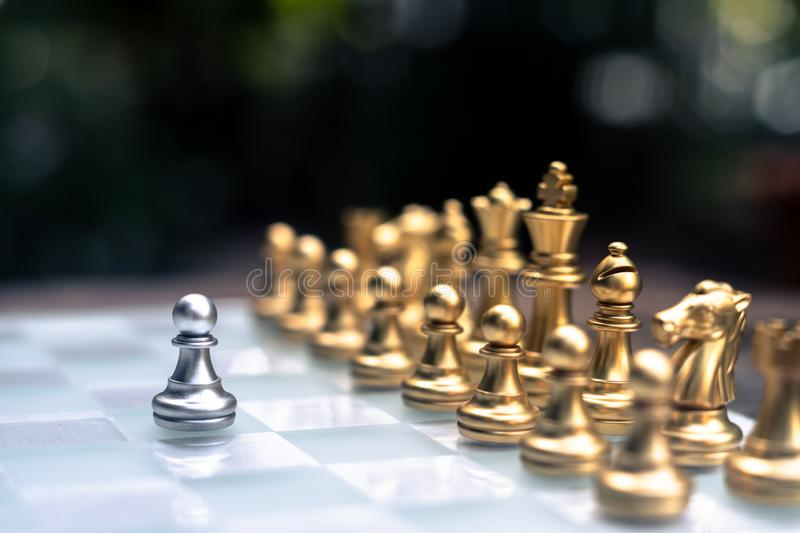 Chess game. A pawn stand determinedly among the enemies. Business competitive concept. Achievement adrenaline ahead ambition brave challenge champion chance royalty free stock photos