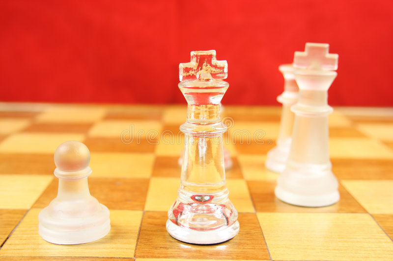 Chess Game with a Red Background. Chess Game - Glass Chess Pieces on a wooden chessboard with a Red background royalty free stock images