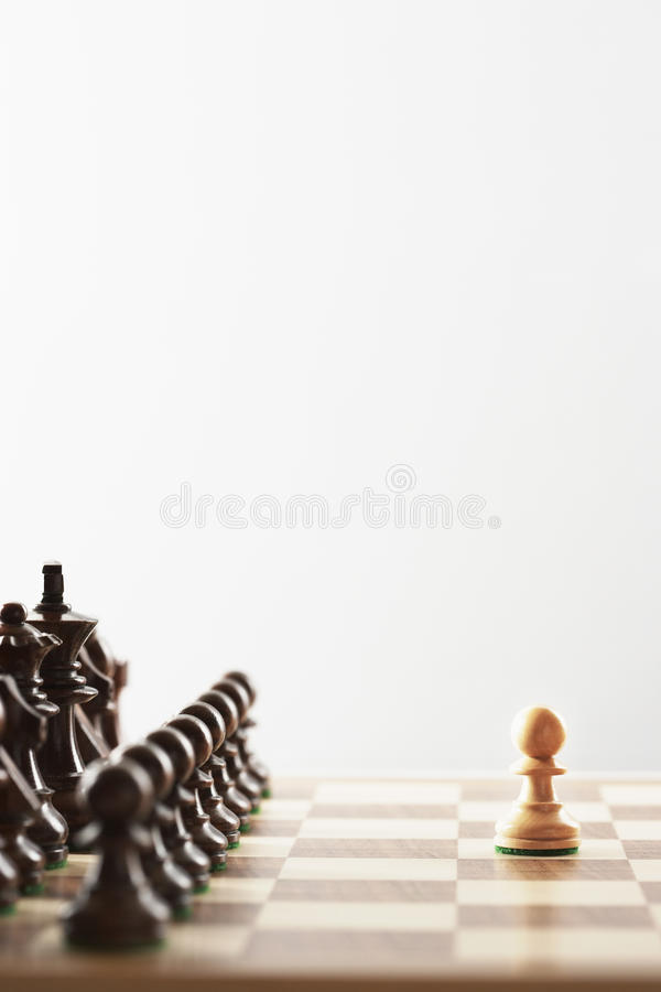 Chess game single white piece in front of black pieces royalty free stock photography