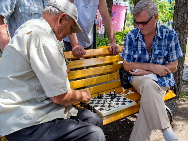 Chess game takes place on a park bench with the participation of spectators stock image