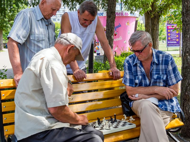 Chess game takes place on a park bench with the participation of spectators royalty free stock photo