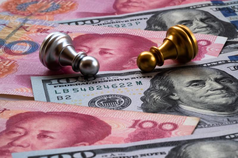 Chess game, two pawns fall down on Chinese yuan and US dollar background. Trade war concept. Conflict between two big countries,. USA and China concept. Copy royalty free stock photo