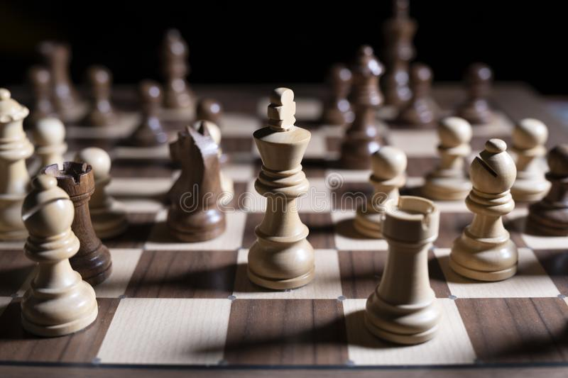 Chess game. White and black pieces are fighting for victory. The Central figure is in focus. The concept of teamwork stock photography